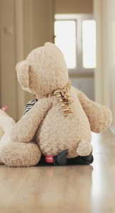 Zwilling Ulf versteckt sich hinter einem riesigen Teddy