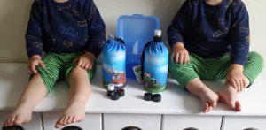 """Die Zwillinge ALf und Ulf mit der Trinkflasche Emil zum """"anziehen""""."""