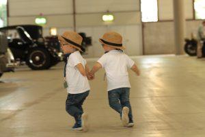 Zwillingjungs, Alf und Ulf rennen in der Oldtimerhalle