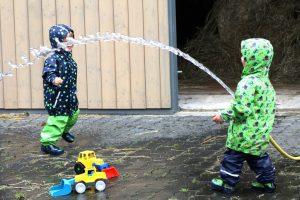 Die Zwillinge Alf und Ulf spielen mit dem Wasserschlauch Feuerwehrmann