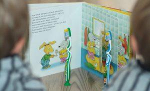 Zwillinge, Alf und Ulf lesen mit ihren Zahnbürsten, Moritz Moppelpo putzt seine Zähne.