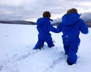 Die Zwillinge Alf und Ulf gehen Hand in Hand im Schnee spazieren.