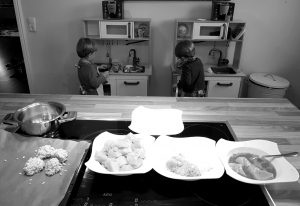 Die Zwillinge Alf und Ulf kochen an ihrer Kinderküche. Im Vordergrund sieht man die Zubereitung von Chicken-Nuggets
