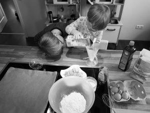 Zwillinge Alf und Ulf messen die Milch ab für ihren Pfannkuchenteig
